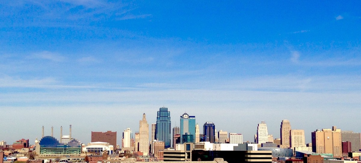 The downtown Kansas City skyline under a typical blue sky with wispy white clouds.